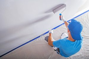 House Painting Contractor with drop cloth and blue tapered wall