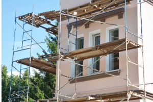 Painting and Plastering Exterior House with scaffolding and wood planks