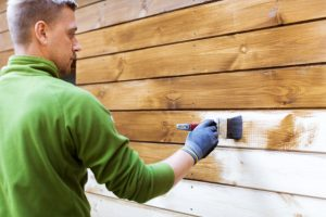 Hillsboro worker painting house exterior with brown wood protective color
